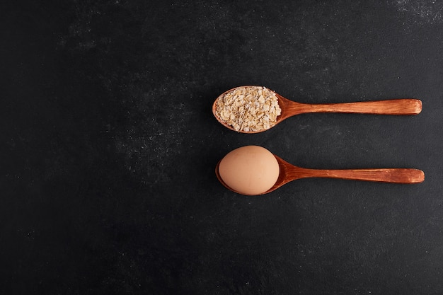 Egg and flour in wooden spoons in parallel style.