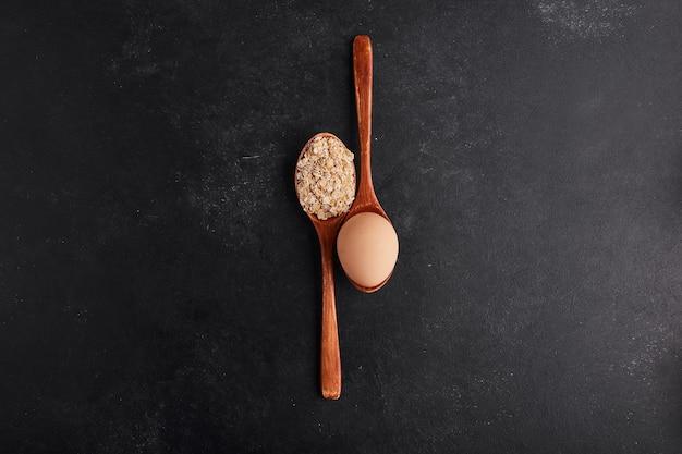 Uova e farina su cucchiai di legno, vista dall'alto.