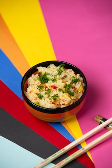 Egg fried rice with bell peppers and dill on colorful background