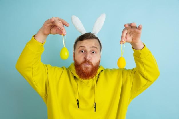 Приближается охота за яйцами. кавказский человек как пасхальный кролик с яркой повседневной одеждой на синем фоне студии. поздравления с пасхой. понятие человеческих эмоций, выражения лица, праздников. copyspace.