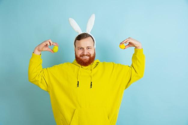 卵狩りがやってくる。青いスタジオの背景に明るいカジュアルな服を着たイースターバニーとしての白人男性。