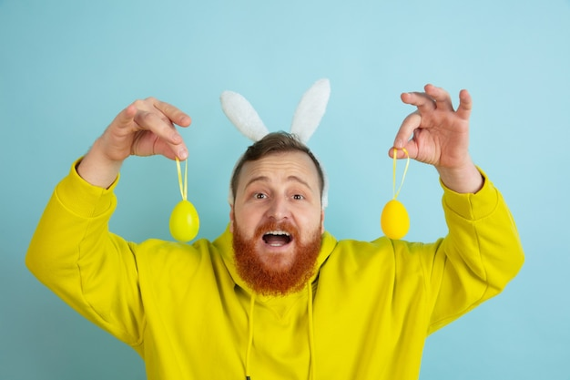 Egg hunt coming. caucasian man as an easter bunny with bright casual clothes on blue studio background. happy easter greetings. concept of human emotions, facial expression, holidays. copyspace.