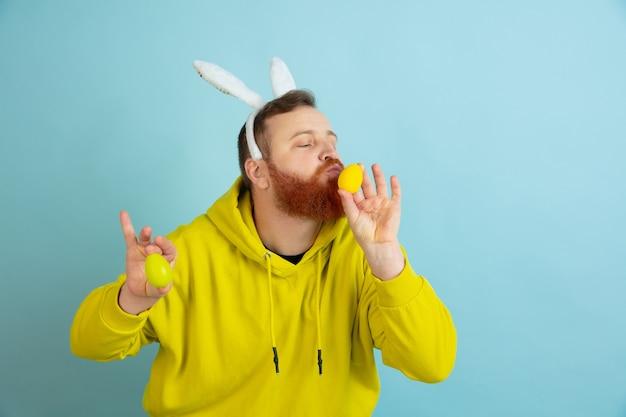 Caccia alle uova in arrivo. uomo caucasico come un coniglietto di pasqua con abiti casual luminosi su sfondo blu studio.