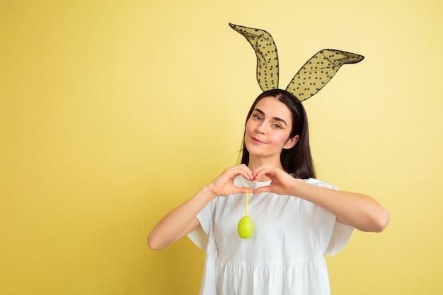 Caccia alle uova in arrivo. donna caucasica come un coniglietto di pasqua su sfondo giallo.