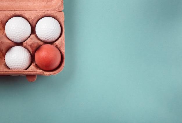 Яйцо в коробке мячей для гольфа, flatlay на синем фоне с большим количеством места для копирования. концепция выбора, конформизма, единства, исключительности, трудного выбора и т. д.