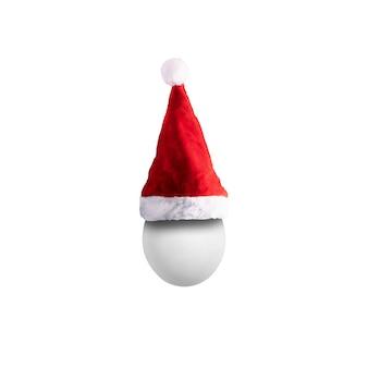 Яйцо в шляпе санта-клауса на белом фоне, концепция счастливого рождества