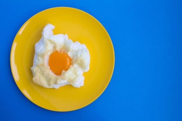 青い背景の黄色いプレートの雲の中の卵。上面図。コピースペース。