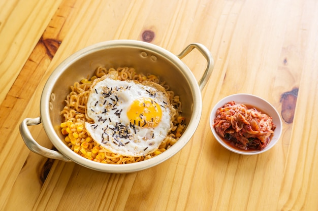 Egg instant noodle and kimchi on a wooden table.