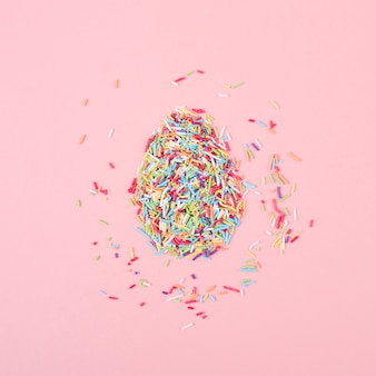 Egg made of colorful sprinkles on table
