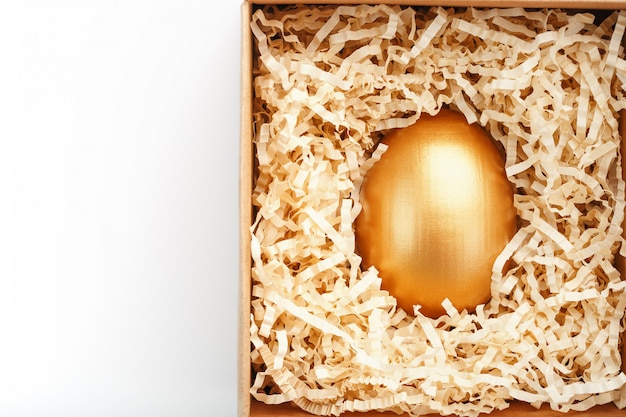 Egg made of gold in a wooden box on a white background. the concept of exclusivity and superprize. minimalistic composition.