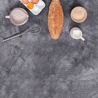 Egg; milk; whisks; loaf of bread; flour and oat bran on concrete backdrop