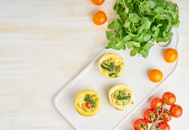 Egg muffins, paleo, keto diet. omelet with spinach, vegetables, tomatoes