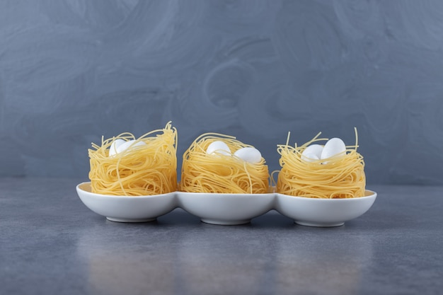 Egg noodle nests with white candies in bowls.