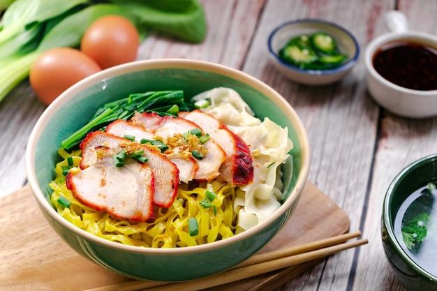 구운 붉은 돼지 고기와 완탕이 들어간 계란 국수와 수프와 달콤한 소스