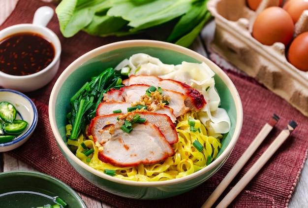 현지의 달콤한 소스와 흰깨와 청 고추를 식초에 곁들인 구운 붉은 돼지 고기를 곁들인 계란 국수-