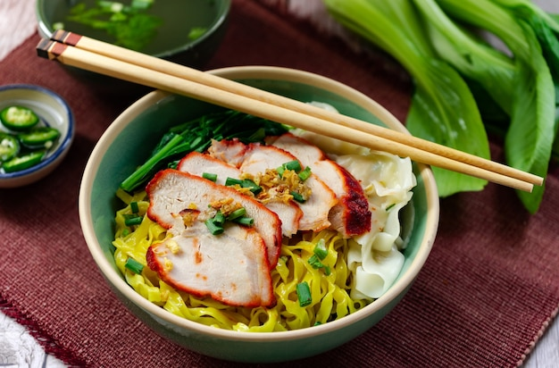 Egg noodle with barbecued red pork serving with local sweet sauce and white sesame and green chili in vinegar -