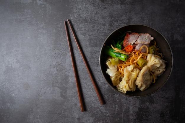 테이블에 붉은 구운 돼지 고기와 완탕 계란 국수.