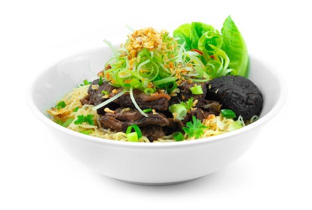 ネギとカリカリにんにくを乗せた牛肉の煮込みと卵麺中華料理スタイルの装飾野菜の側面図
