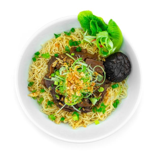 ネギとカリカリにんにくを乗せた牛肉の煮込みと卵麺中華料理スタイルの装飾野菜のトップビュー
