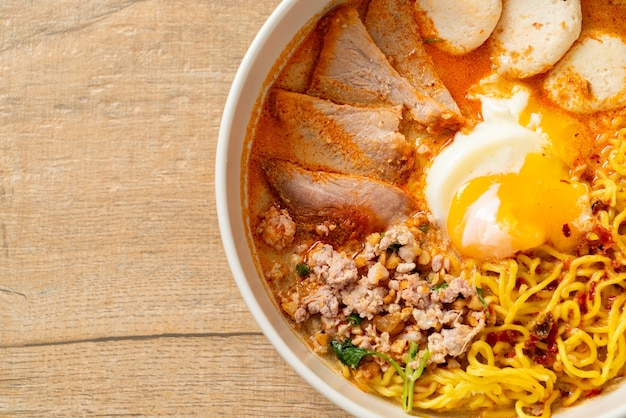 Egg noodles with pork and meatball in spicy soup or tom yum noodles in asian style