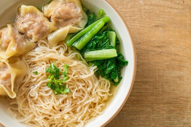 Яичная лапша со свиным супом вонтон или суп из свиных пельменей и овощами - стиль азиатской кухни