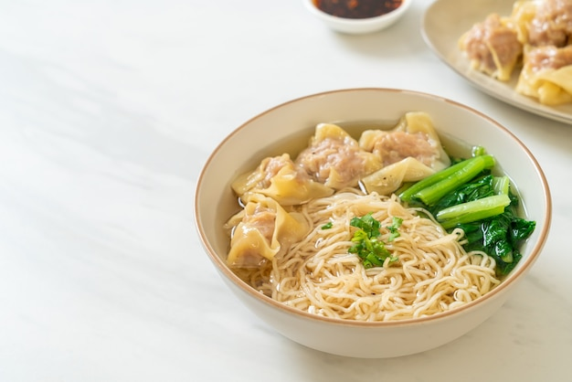 Egg noodles with pork wonton soup or pork dumplings soup and vegetable - asian food style