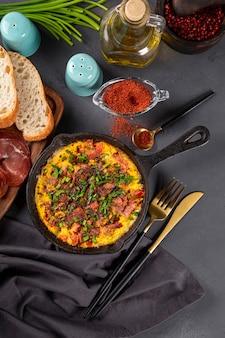 ソーセージと調味料を入れた卵焼きオムレツを鋳鉄鍋の上面図、垂直写真に。
