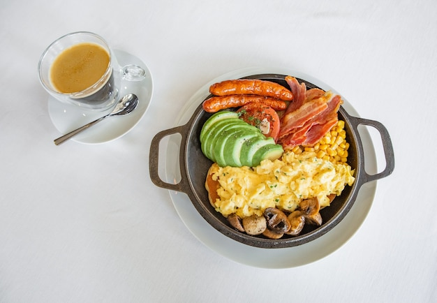 Egg omelet with sausage and meat and vegetables cucumber tomato and coffee with milk