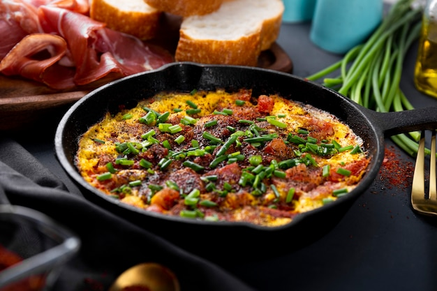 Egg omelet with sausage and seasonings in a cast iron pan close up, soft focus.