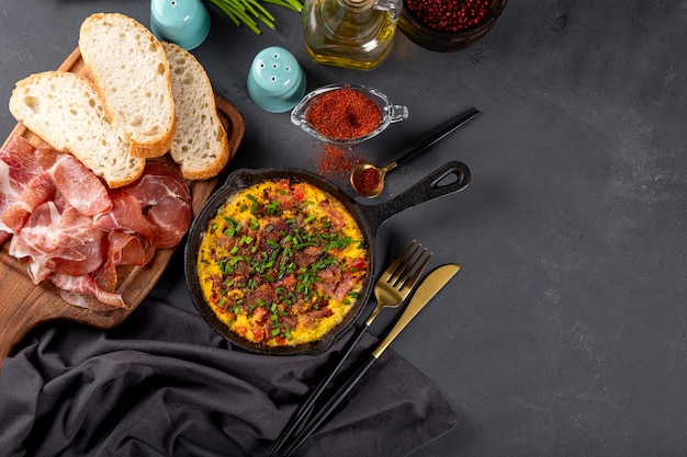 Egg omelet with sausage and seasonings in a cast iron pan top view free space for text.