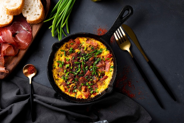 Egg omelet with sausage and seasonings in a cast iron pan top view.