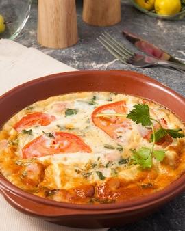클레이 접시에 토마토와 허브를 넣은 계란 오믈렛