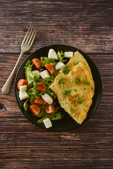 Egg omelette with cherry tomato, mozzarella and green salad. wooden table with copy space.