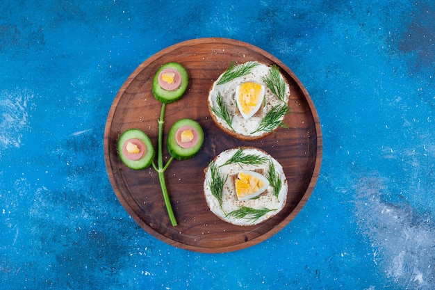 青いテーブルの上に、皿の上のきゅうりのチーズパンソーセージの卵。
