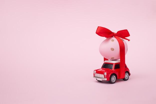 Яйцо на красной игрушечной машинке на розовой пастельной стене