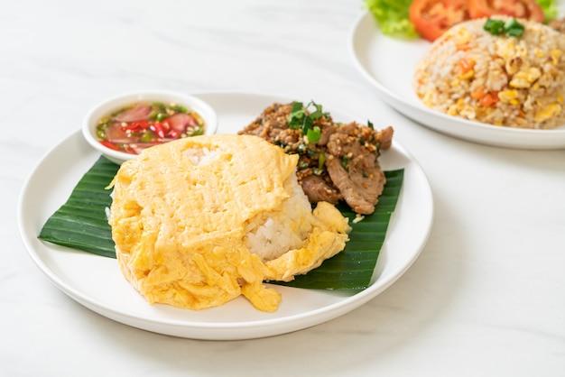 豚肉のグリルとスパイシーソースをトッピングしたご飯に卵-アジア料理スタイル