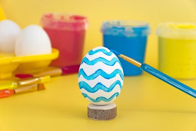 黄色い卵トレイに卵と青い波で描かれた卵、