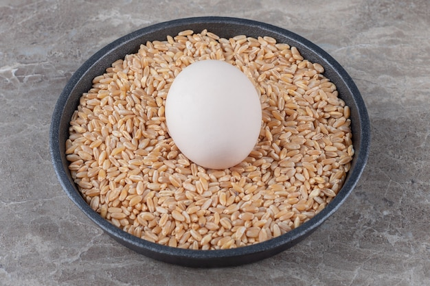 Egg and pile of barley on black plate.
