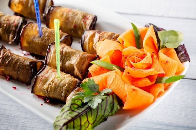 Egg-plant roll with cheese and nice rose like carrot on white plate with selective focus