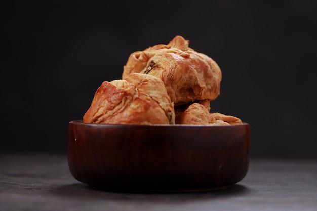 スパイシーでおいしい卵マサラを詰め、木製の食器の上に置いたエッグパフペストリー