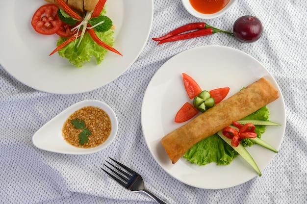 Egg roll or fried spring rolls on the white plate thai food. top view.