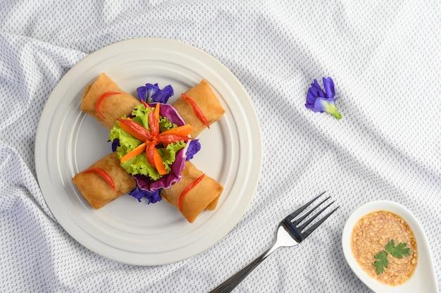 白いプレートタイ料理の卵ロールまたは揚げ春巻き。上面図。