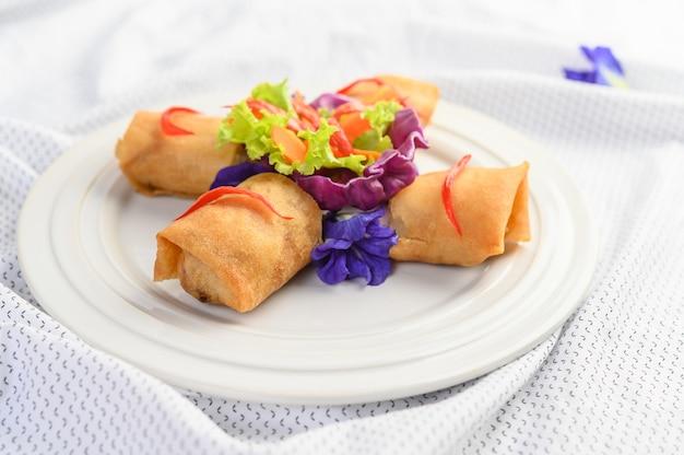 白いプレートタイ料理の卵ロールまたは揚げ春巻き。 。