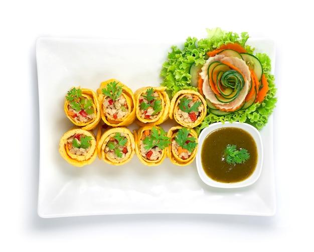 Яичный рулет, фаршированный куриным морковным луком и чили, подается со соусом чили, приготовленным