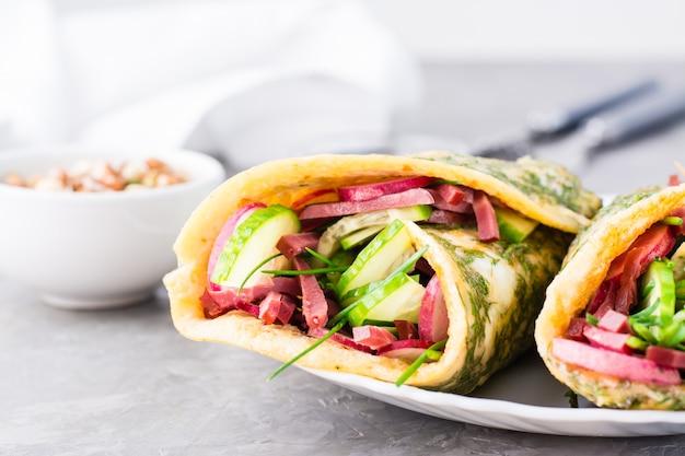 Булочки с начинкой из пастрами, овощами и зеленым луком на тарелке на столе.