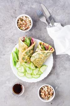 Яичные рулеты, наполненные пастрами, овощами и зеленым луком на тарелке, проросшие зерна и соевый соус в мисках на столе.