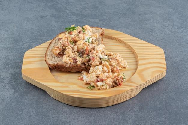 木の板にエッグサラダとパン。