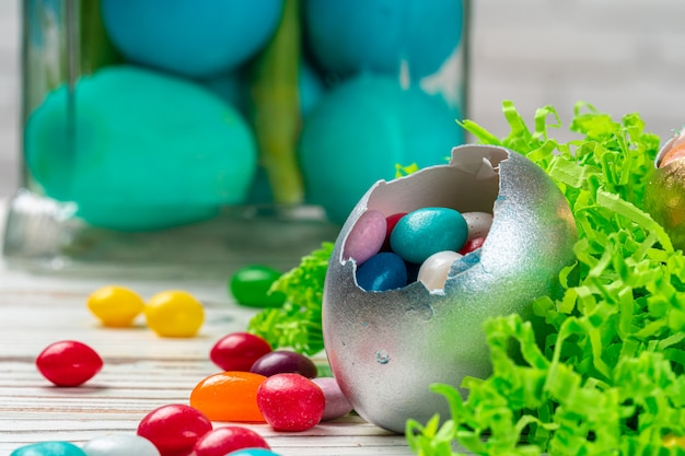 Egg shell with colorful candies inside  in a decorative easter nest