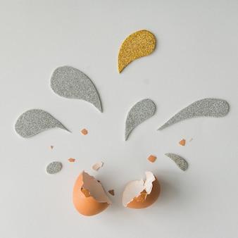Яичная скорлупа с серебряными и золотыми блестящими вкраплениями на белой поверхности