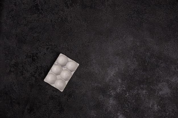 黒のテクスチャ背景に白いコンクリートで作られた卵スタンド。